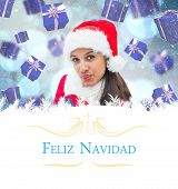 festive brunette blowing against Christmas greeting card