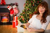 Relaxed redhead reading on the couch at christmas at home in the living room
