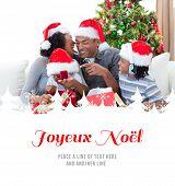 Happy family having fun with Christmas presents against joyeux noel