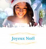 sexy santa girl opening gift against Christmas greeting card