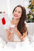 Smiling brunette holding a mug against snow falling