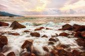 Big boulders and sea waves at sunrise
