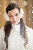 Pretty brunette with ear muffs smiling at camera against snow falling