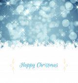 Christmas greeting card against shimmering light design on blue