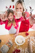 Festive mother and daughter making christmas cookies against snow falling