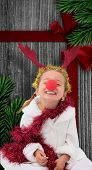 Cute little girl wearing red nose and tinsel against wood with festive bow