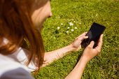 Pretty redhead text messaging on her phone lying on grass