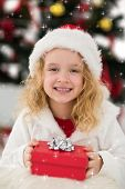 Festive little girl holding a gift against twinkling stars