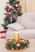 Candle and wreath on table for christmas against twinkling stars