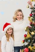 Festive mother and daughter decorating christmas tree against snow falling