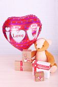 Teddy bear takes gifts and love heart balloon on wooden table, on the brick wall background