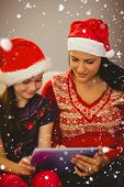 Festive mother and daughter using tablet against snow falling