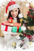 Festive brunette holding pile of gifts near a christmas tree against christmas theme frame in silver