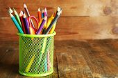 Colorful pencils with scissors in metal holder on rustic wooden background