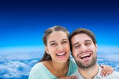 Cute couple smiling at camera against blue sky over clouds at high altitude