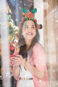 Smiling brunette in christmas hat holding mug against snow falling