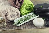 Branches of rosemary on towels, massage bags and spa stones on wooden background. Rosemary spa concept