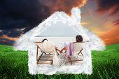 Couple looking ocean on their deck chairs against green field under orange sky