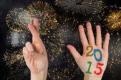 Hands against colourful fireworks exploding on black background