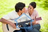 Man and his friend look at each other while he is playing the guitar against house outline