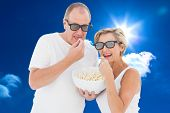 Mature couple wearing 3d glasses eating popcorn against bright blue sky with clouds