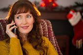 Cheerful redhead on the phone at christmas at home in the living room