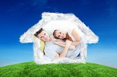 stock photo of caress  - Caress young couple lying together on the sofa in the livingroom against green hill under blue sky - JPG
