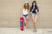 Two beautiful and young girlfriends having fun with a skateboard, in front of a brick wall