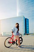stock photo of bicycle gear  - Attractive young woman win fixed gear bike posing outdoors with beautiful skyscraper on background pretty young brown haired woman standing with her modern pink bicycle in city stylish hipster girl - JPG