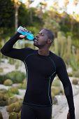 Attractive fit man in active clothes refreshing with water after run