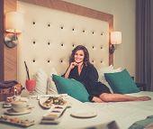 Beautiful woman having breakfast in a hotel room