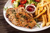 Pork chops, French fries and vegetables