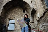 stock photo of gothic  - Beautiful tourist woman on vacation with a map in gothic quarter young tourist girl holding city map in the hands smiling charming girl studying city map standing in gothic quarter in Barcelona - JPG