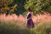 Smiling Pregnant Woman Standing In Colorful, Lush Foliage