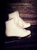 White Ice Skates on wooden background