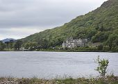 Kylemore Abbey in mountains on the lake.