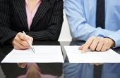 picture of contract  - businessman and businesswoman are inspecting contract in suit - JPG