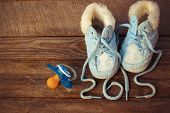 2015 year written laces of children's shoes and a pacifier on the old wooden background. Toned image