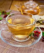 Tea with lingonberry in glass cup on bamboo napkin