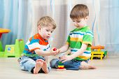 children brothers play together in nursery