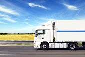 stock photo of moving van  - truck with freight moving fast on road - JPG
