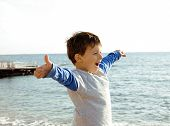 little cute boy on sea coast thumbs up
