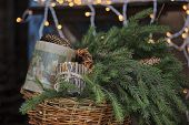 Christmas box of pine cones, wooden candle holder and fir branches