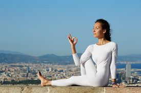 stock photo of yoga  - Yoga on high altitude with big city on background young woman seated in yoga pose on amazing city background - JPG