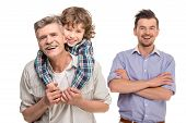 picture of grandfather  - Grandfather giving piggyback ride to his son on background father - JPG