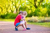 pic of little young child children girl toddler  - Happy children hugging and playing in a park laughing boy and his funny curly toddler sister adorable little girl having fun in a sunny autumn park - JPG