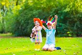 stock photo of horse girl  - Two happy kids laughing boy dressed as native American with colorful feather hat and little curly toddler girl in yellow boots with a toy horse playing cowboy outdoors on a sunny summer day - JPG