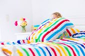pic of striping  - Cute funny little toddler girl sitting in a white bed with colorful rainbow stripe pillow and cover sheet playing hide and seek on a sunny morning at home