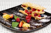 picture of custard  - Millefeuille with berries and caramel custard on a dark plate - JPG