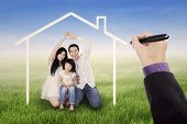 image of dream home  - Beautiful family sitting on the meadow under a dream home shot outdoors - JPG